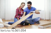 Купить «Couple taking out wood flooring from package», видеоролик № 6061054, снято 31 января 2014 г. (c) Syda Productions / Фотобанк Лори