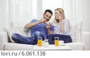 Купить «Smiling couple having breakfast at home», видеоролик № 6061138, снято 16 февраля 2014 г. (c) Syda Productions / Фотобанк Лори