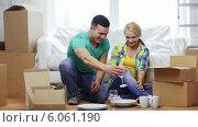 Smiling couple unpacking boxes with kitchenware. Стоковое видео, видеограф Syda Productions / Фотобанк Лори