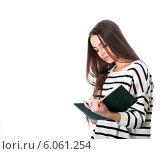 Девушка что-то записывает в тетради на белом фоне. Стоковое фото, фотограф Виктор Аксёнов / Фотобанк Лори