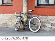 Велосипед, припаркованный на тротуаре, привязан цепью к водосточной трубе. Редакционное фото, фотограф Vladimir Sviridenko / Фотобанк Лори