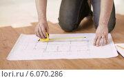 Купить «Close up of male hands measuring blueprint», видеоролик № 6070286, снято 10 февраля 2014 г. (c) Syda Productions / Фотобанк Лори
