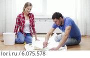 Купить «Smiling couple smearing wallpaper with glue», видеоролик № 6075578, снято 31 января 2014 г. (c) Syda Productions / Фотобанк Лори