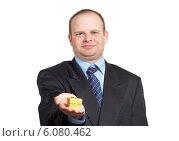 Молодой мужчина в деловом костюме держит на ладони золотистый подарок. Стоковое фото, фотограф Александр Власик / Фотобанк Лори