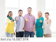 Купить «happy creative team showing thumbs up in office», фото № 6087974, снято 17 мая 2014 г. (c) Syda Productions / Фотобанк Лори