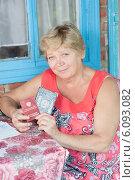 Пожилая женщина с паспортом и пенсионным удостоверением в руках. Стоковое фото, фотограф Типляшина Евгения / Фотобанк Лори