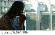 Купить «Задумчивая женщина у окна на фоне большого города», видеоролик № 6094986, снято 29 мая 2014 г. (c) Данил Руденко / Фотобанк Лори