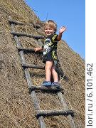 Мальчик на стоге сена в русской деревне (2012 год). Редакционное фото, фотограф Евгений Суворов / Фотобанк Лори