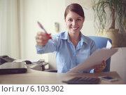 Купить «Молодая деловая женщина сидит за столом в офисе, протягивая ручку для подписи документов», фото № 6103902, снято 28 июня 2014 г. (c) Олег Шеломенцев / Фотобанк Лори