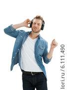 Купить «Handsome of a young man enjoying music», фото № 6111490, снято 4 ноября 2013 г. (c) Wavebreak Media / Фотобанк Лори
