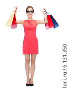 Купить «smiling woman in red dress with shopping bags», фото № 6131350, снято 1 июня 2014 г. (c) Syda Productions / Фотобанк Лори