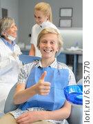Купить «Teenager patient thumbup at dental surgery dentist», фото № 6135770, снято 22 июня 2014 г. (c) CandyBox Images / Фотобанк Лори