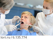 Купить «Dentist and assistant with scared teenage patient», фото № 6135774, снято 22 июня 2014 г. (c) CandyBox Images / Фотобанк Лори