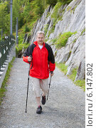 Купить «Мужчина в возрасте идет по горной дороге с трекинговыми палками», фото № 6147802, снято 30 июня 2014 г. (c) Юлия Кузнецова / Фотобанк Лори