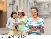 Купить «smiling teenage girls with city guides and camera», фото № 6149950, снято 25 мая 2014 г. (c) Syda Productions / Фотобанк Лори