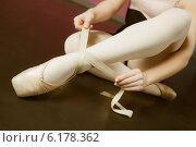 Ballerina tying the ribbon on her ballet slippers. Стоковое фото, агентство Wavebreak Media / Фотобанк Лори