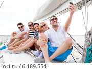 smiling friends sitting on yacht deck. Стоковое фото, фотограф Syda Productions / Фотобанк Лори