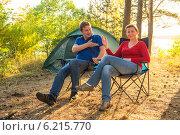 Купить «Пара сидит возле палатки в кемпинге», фото № 6215770, снято 12 июля 2014 г. (c) Константин Лабунский / Фотобанк Лори