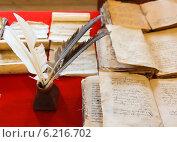 Купить «Перья в чернильнице на столе со старыми книгами», фото № 6216702, снято 20 июля 2018 г. (c) Mikhail Starodubov / Фотобанк Лори