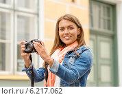Купить «smiling girl with digiral photocamera in the city», фото № 6217062, снято 14 июня 2014 г. (c) Syda Productions / Фотобанк Лори