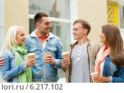 group of smiling friends with take away coffee. Стоковое фото, фотограф Syda Productions / Фотобанк Лори