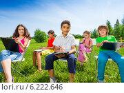 Купить «Группа детей сидит с планшетами для бумаг на природе», фото № 6222646, снято 8 июня 2014 г. (c) Сергей Новиков / Фотобанк Лори