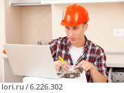 Мужчина в строительной рассчитывает смету ремонта на ноутбуке. Стоковое фото, фотограф Astroid / Фотобанк Лори