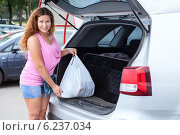 Молодая девушка складывает покупки в багажник автомобиля. Стоковое фото, фотограф Кекяляйнен Андрей / Фотобанк Лори