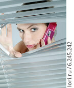 Woman's portrait while looking out the blinds. Стоковое фото, агентство BE&W Photo / Фотобанк Лори