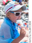 Купить «Девочка в тёмных очках ест мороженое на пляже», фото № 6261934, снято 30 июня 2014 г. (c) Николай Мухорин / Фотобанк Лори