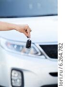 Купить «Женская рука держит ключ зажигания на фоне капота автомобиля», фото № 6264782, снято 20 июля 2014 г. (c) Кекяляйнен Андрей / Фотобанк Лори