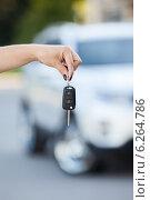 Купить «Ключ от автомобиля в вытянутой руке на фоне машины», фото № 6264786, снято 20 июля 2014 г. (c) Кекяляйнен Андрей / Фотобанк Лори