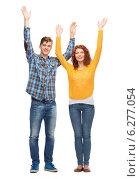 Купить «smiling teenagers with raised hands», фото № 6277054, снято 22 июня 2014 г. (c) Syda Productions / Фотобанк Лори