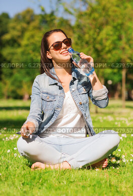 smiling young girl with bottle of water in park