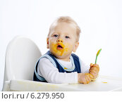 Купить «Little boy while eating and sitting in a highchair.», фото № 6279950, снято 24 мая 2019 г. (c) BE&W Photo / Фотобанк Лори