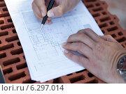 Строитель делает отметки на плане этажей. Стоковое фото, фотограф Светлана Пальцева / Фотобанк Лори