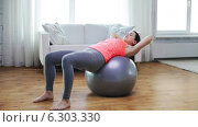 Купить «Girl exercising with fitness ball at home», видеоролик № 6303330, снято 15 апреля 2014 г. (c) Syda Productions / Фотобанк Лори