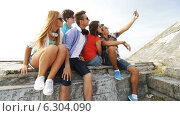 Купить «Group of smiling teenagers making selfie outdoors», видеоролик № 6304090, снято 12 августа 2014 г. (c) Syda Productions / Фотобанк Лори
