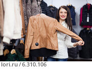 Купить «Cute young woman choosing jacket at clothing store», фото № 6310106, снято 28 января 2014 г. (c) Яков Филимонов / Фотобанк Лори