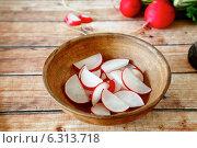 Купить «Нарезанный редис в деревянной тарелке на столе», фото № 6313718, снято 5 мая 2014 г. (c) Афанасьева Ольга / Фотобанк Лори