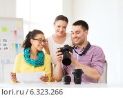 Купить «smiling team with photocamera working in office», фото № 6323266, снято 17 мая 2014 г. (c) Syda Productions / Фотобанк Лори