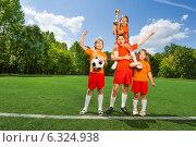 Купить «Победители. Дети в спортивной форме стоят с кубком и футбольным мячом на поле», фото № 6324938, снято 9 июля 2014 г. (c) Сергей Новиков / Фотобанк Лори