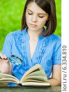 Купить «Young woman close-up reading book magnifier», фото № 6334810, снято 30 июня 2011 г. (c) BestPhotoStudio / Фотобанк Лори