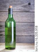 Купить «Бутылка белого вина с пробкой на деревянном фоне», фото № 6335918, снято 26 августа 2014 г. (c) Анатолий Типляшин / Фотобанк Лори