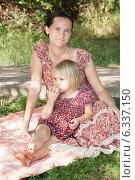 Мама с дочкой сидят на пледе в парке. Девочка держит в руке яблоко. Стоковое фото, фотограф Мороз Елена / Фотобанк Лори