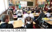 Купить «Учительница учит правильно сидеть за партами детей первоклассников. 1 Сентября», видеоролик № 6354558, снято 1 сентября 2014 г. (c) Кекяляйнен Андрей / Фотобанк Лори