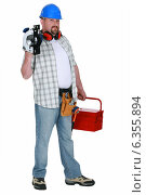 Tradesman holding a circular saw and his toolbox. Стоковое фото, фотограф Phovoir Images / Фотобанк Лори