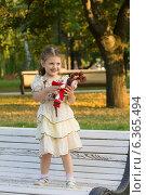 Купить «Красивая девочка позирует в парке стоя на скамейке с игрушкой в руках», фото № 6365494, снято 18 июля 2014 г. (c) Алексей Назаров / Фотобанк Лори