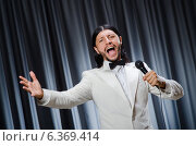 Купить «Man singing in front of curtain in karaoke concept», фото № 6369414, снято 14 июля 2014 г. (c) Elnur / Фотобанк Лори