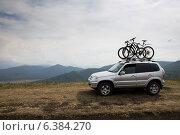 Горный туризм, Внедорожник с велосипедами на фоне гор и пасмурного неба (2014 год). Редакционное фото, фотограф Максим Кожушко / Фотобанк Лори